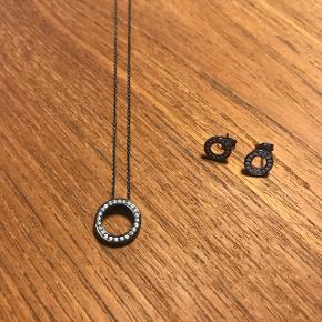 Scrouples halskæde og ørestikker i sort rhodineret sølv. Længden på halskæden er 42 cm, med forlænger stykke så den kan blive op til 45 cm.  Cirklen på ørestikkerne har en diameter på 9 mm. Sælges samlet eller hver for sig.