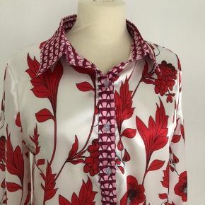 Retro satinskjorte i hvid med røde blomster som motiv.  Ved ærmer, kraven og langs knaplukningen foran er motivet lilla og lyserødt.  Længde fra skulder er 58 cm, og brystmålet er 96 cm.   Mærke er ukendt.  Vaskeanvisning mangler, men er sandsynligvis fremstillet af polyester. Ellers bærer skjorten ikke præg af brug.