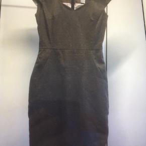 Mærke: H&M Størrelse: 34, passer også str 36 Farve: sort grå beige Materiale: 64% polyester, 34 viscose Kjolen: har et flot klassisk snit, med et kort ærme. Kjolen er foret og stoffet virker lidt kraftigt Stand: aldrig brugt  Sælges kr 50 Bytter ikke Sætter pris på tilfredse købere