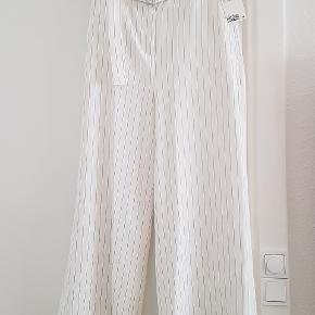 Fine stribede bukser fra h&m, ubrugt, med prismærke. Hvide med små sorte striber. 3/4 lange og højtaljede, vide ben. Perfekte til sommer 🤗 BYD gerne.