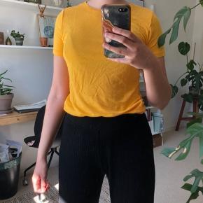 Flot gul/orange T-shirt, meget tyndt stof, som er perfekt til varmere sommerdage. Dog er den en smule gennemsigtig.  Aldrig brugt, kun vasket én gang.