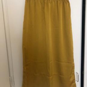 Smuk lang nederdel i silkelignende materiale fra HM. Str. 34, fremstår som ny.