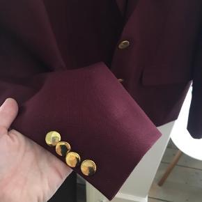 Skræddersyet blazer i flot bordeaux farve med guldknapper. Ca. str. 52, svarer ca. til str. L. To lommer udenpå samt to inderlommer. Brugt få gange og i virkelig god stand.