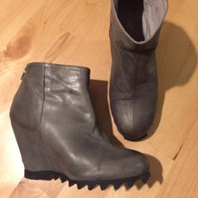 Kilhælsstøvler i grå med sort sål. Størrelse 39. Lynlås bagpå. Blødeste læder. Sålen er sort med råt look. De er lavet i Portugal.