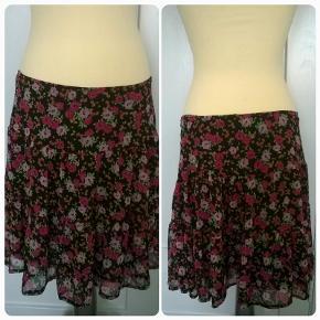 Sød tynd nederdel m/sort skørt, fast bærestykke i talje/hofte, lynslås venstre side.(v billede for/h bag) 50 cm lang, talje 90 cm (aldrig brugt)/Mrkt: Units/Str: 42/Farve: Sort,lilla,pink,grøn,orange/Pris: kr 50,-