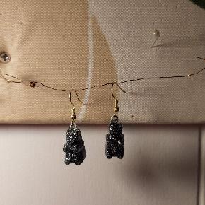 Hjemmelavede øreringe der ligner små vingummibamser i sort med sølv glimmer også er de sølv/guld glimmer malede bagpå