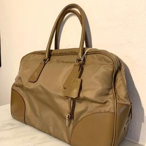 Smuk Prada taske, som er perfekt til arbejde eller studie.  Mål: 40x26x10 cm   Der er brugsspor og lidt slid i bundens hjørner men ellers i god stand. Pris er sat derefter. Bud er velkomne.   Købt på vestaiare Collective og med aut. bevis derfra.