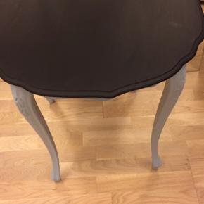 Fint træbord malet i koksgrå og lyseblå. Mål 60 cm i diameter og 58 cm i højden. Har fine små detaljer😊