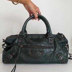 Lidt om tasken 👜 Balenciaga Twiggy taske i en elegant mørkegrøn farve, perfekt farve her til efteråret. Tasken kan både bruges som skuldertaske og crossbody. Kan lige præcis holde en MacBook pro 13 tommer.  Der medfølger original dustbag samt spejl til tasken.   Stand 💬 Tasken fremstår generelt i super god stand, farven er ikke synligt famlet nogle steder på tasken og håndtaget bærer ikke præg af slid. Der er dog noget slid på hjørnerne/kanterne.   Autencitetsgaranti ☀️ Alle tasker autencitetstjekkes inden salg, vha. specifikke indikatorer på tasken som kan vise om den er ægte. Du kan derfor være tryg ved, at du investerer i et autentisk produkt!  Kun seriøse bud tak 🙌  Mængderabat gives ved køb af flere ting✨