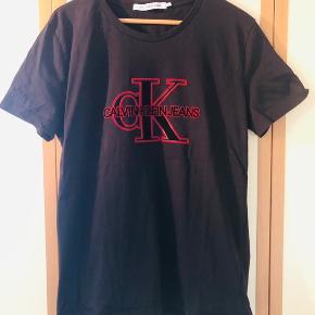 Helt ny T-shirt med stort print for fra Calvin K. sælges da den er købt i for stor str. T-shirten er fremstillet i dejligt blødt stof, med kraftigt print. Fremstår helt som ny da den aldrig har vært i brug.  Giv et fair bud