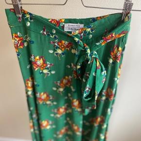 Fin grøn nederdel med blomster - perfekt til efteråret med en strik til.  Nederdelen er i 100% viskose, har et bindebånd og lukkes med lynlås og knap.   Knappen sidder lidt løst og skal evt. lige sys.