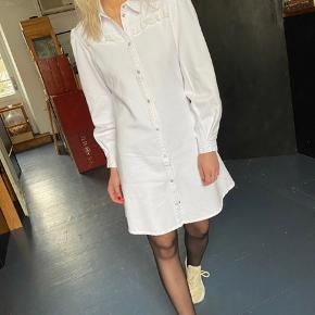 Smuk hvid kjole i en skøn bomuldskvalitet i denim look.æ fra Resume' Brokeback kollektion 2020. Kjolen er a-formet med en smule puff ved skulderen, knaplukning hele vejen ned foran samt en sød blonde detalje over brystet.  Kjolen er aldrig brugt og ligger stadigvæk i silkepapir. Kommer fra et ikke ryger og ikke dyre hjem.  Mål: Bryst omkreds: 94cm  Længde: 90 cm   100% bomuld  Respekter venligst at jeg ikke bytter og køber betaler porto samt gebyr ved tspay.