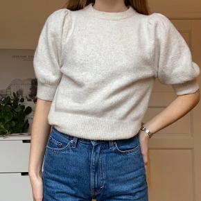 Strikker trøje med pufærmer.  Polyester 52% akryl 38% og uld 8%  Vaskes ved 30 grader.  Den er næsten ikke brugt og kun vasket 1 gang