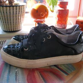 Super cool billi bi sneaker sko med præget lak detaljer på snuden, samt hæl. Skoen har bredde satinsnørebånd der giver et feminint modspil til den 3 cm høje gummi sål. Brugte men velholdte 220pp
