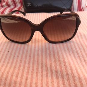 Supercool Chanel solbriller med flotte sølvdetaljer på stængerne. Brune med sort hardbox og hvid Chanel pudseklud.