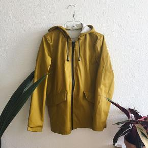Regnjakke i så flot, oliven gul farve. Med tæt lynlås, god størrelse lommer, hat og snørrer i halsen.   Kan sendes, prøves og mødes og handle :-)