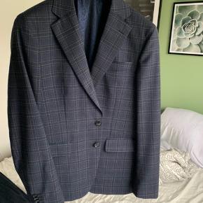 Lækkert jakkesæt fra SAND Copenhagen. Jakkesættet er brugt få gange på kontor. Der er ikke lavet tilretninger hos Skrædder, sættet er derfor ligesom hvis du køber en str. 52 i SAND. Nyprisen er 4500 kr. for dette jakkesæt.