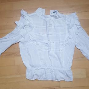 Hvid fin bluse fra Mango med mange flotte detaljer som flæser og knappelukning på ryggen.   Kun brugt ganske lidt og ikke med synlig slitage. 100% viskose.