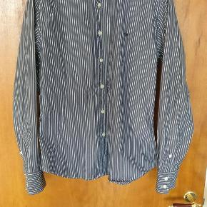 Varetype: mænd skjorte Farve: Blå  fed ældre model fra Burberry med cutaway krave, skjorten er i god stand med enkelte slitage mærker se sidste billede -slid på metal emblem og blå streg streg men ellers står den skarp
