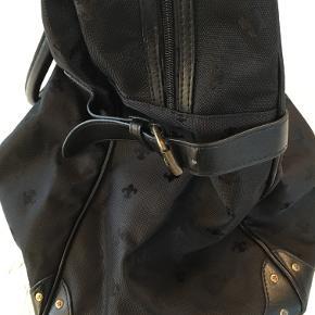 Friis & Co.  Dejlig stor og rummelig rejsetaske i sort stof med mønster af franske liljer, med smarte remme i siderne, samt navn/adresse tag. Tasken har to hanke, lynlåslukning, et stort rum, samt indvendig lomme med lynlås.  Rejsetasken har kun været brugt 1 gang og fremstår derfor yderst fin, ren og velholdt.  Udvendige ca. mål: H: 42 cm. L: 40/45 cm. D: 10/23 cm.  Ny pris: 899,- kr.  Sælges for kun: 350,- kr.