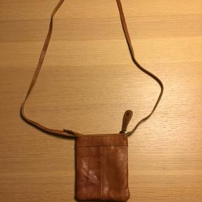 Lille og velholdt cross-body taske fra Pieces i den fineste brune/rustfarvede læder. Fine detaljer med 3 lynlåslommer, heraf 2 foran, mens den sidste sidder i toppen af tasken.   Måler 12 cm. i bredden og 15 cm. i toppen.   Køber betaler porto.