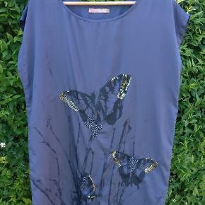Sød kjole i dyb blå farve og med sommerfugleprint og perlebroderi.  Kan bruges løs eller med et bælte i livet.  Brugt, men i pæn stand. Der er en lille fejl ved højre skulder, se billede.