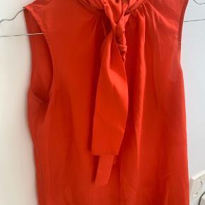 Fineste røde top med pussy bow i halsen, og lynlås i nakken. Smart både til jakkesæt og jeans :) Passer en str. 34/36