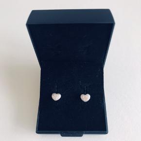 De fineste små hjerteøreringe i sølv :-) Størrelse ca. 6 mm. Der er lidt slid på det ene hjørne på den ene ørering- se billede. Derfor også den billige pris. Prisen er uden forsendelse.