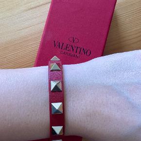 """Rødt læder armbånd med nitter fra Valentino sælges, da jeg desværre ikke får det brugt.  Standen er """"Næsten som ny"""". Da det var en gave, har jeg desværre ikke kvitteringen, men der følger original æske samt ekstra nitter med.   Realistiske bud modtages gerne.  Nyprisen var omkring 1200 kroner."""