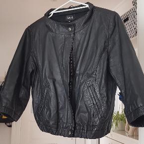 Fed Bolero style læderjakke med trykknapper, lynlås og gode lommer. Det er 3/4 ærmer. Ærmer: 41cm Længde: 47cm BM: 2x52cm
