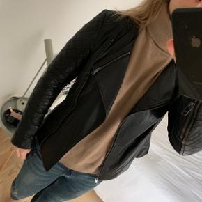 DKNY jakke i lammeskind, den er i størrelsen petite, hvilket svarer til en xs. Elastisk stof på undersiden af ærmerne og lidt i siderne, se sidste billede.  Længde på jakken målt bagpå er ca. 55 cm.  Bytter ikke!
