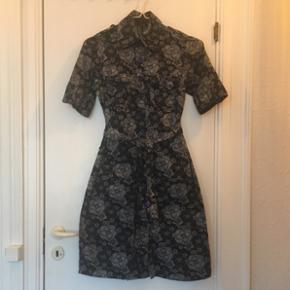 Fin skjortekjole i mørkeblåt blomstret print. Kjolen har krave, knapper foran og bindebånd i taljen.  Aldrig brugt - vasket en enkelt gang.