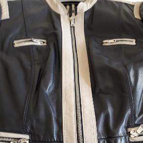 """Flot og speciel jakke i bikerstil. En af mine yndlingsjakker, som jeg har i flere størrelser. Denne er blevet for lille. Den er i en flot lødig marineblå farve (selvom det ses dårligt på billedet – Marine er svært at fotografere, farven ser kedelig ud. Det er den bestemt ikke).  Farven på Torsoen, er som den ser ud i virkeligheden. Jakken har envejs lynlås og Hardwaren er """"sølv"""" Den er """"smør""""blød Den oprindelige købspris er ved køb i Danmark. Jeg har faktisk købt den i Tyskland for 299 euro (=2500 kr.)  Jakkens mål: Bryst 106 cm. Bund 106 cm. Krave 3 cm. Ærme 62 cm. Længde 58 cm. Lynlås 55 cm.  Se også mine andre varer. Hvis du køber 3 artikler er den billigste GRATIS!"""