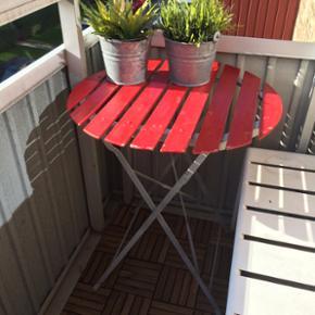 Cafebord med gråt stel og rød bordplade. Måler 60cm i diameter  Det ene hjørne er desværre knækket