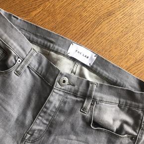 Næsten nye jeans fra The Lab. Fremstår helt nye og uden brugsspor.  Lynlås detalje ved anklerne. Str 28.  Kan afhentes i Århus eller Vejle, eller sendes med DAO:)