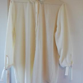 Fin skjorte i tyndt stof. Råhvid/creme i farven. En anelse gennemsigtig. Korte ærmer samt fin binde-detalje ved ærmerne. Kun brugt én gang. Tager ikke billede af tøjet på 🌺