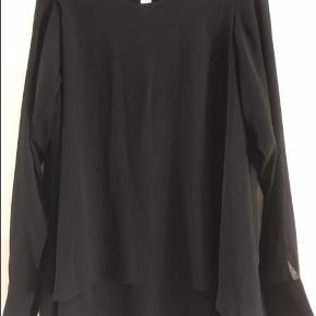 Varetype: Bluse med transparante ærmer. Farve: Sort  Løs bluse i lag med forsk. længde, som giver den et flot fald. Ærmerne er gennemsigtige. Kan bruges som den er eller med bælte. Få god rabat ved køb af mere.