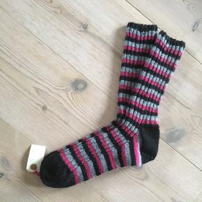 Håndstrikkede sokker str. 40 i sort, grå og pink.  70% uld og 30% polyamid  Prisen er fast.