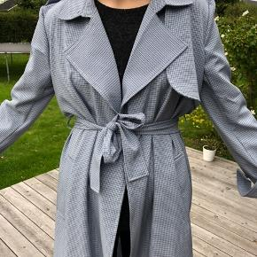 Trenchcoat i blå-ternet Den er brugt enkelte gange men har ingen brugstegn. Den er ikke blevet vasket Købt for 640 Minimumspris er 200