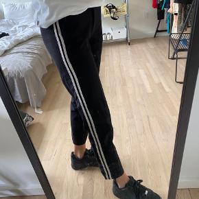 Sorte habitbukser med striber ned langs benene. Fra sisters point