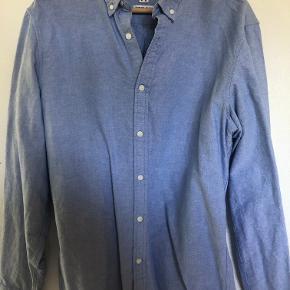 Lækker klassisk skjorte fra Pull & Bear i oxford kvalitet.  Kvalitet: 100% Bomuld Bredde: 58cm. (Bryst) Længde: 81cm. (Ned over ryggen) Ærmelængde: 54cm. (fra armhulen og ned til manchetten)