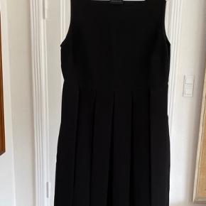 Den lille sorte, klassisk figursyet kjole med brede bånd i underdelen Modellen er tætsiddende og de brede bånd gør  kjolens figur ekstraordinært elegant Stoffet er kraftigt - en vinterkjole Ingen brugstegn