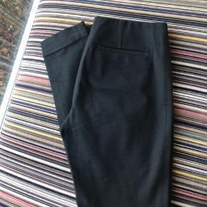 Lækre bukser i en skøn kvalitet med stræk. De har lynlås i siden og fast elastik i taljen. De har fine lommer bagpå og sidder fantastisk. De har kostet 650kr. De er meget velholdte og fremstår uden brugsspor.