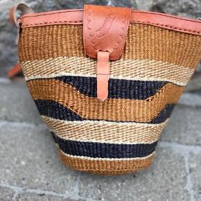 Smuk, håndlavet sisaltaske med detaljer af ægte læder. Læderremmen kan justeres til den ønskede længde. Åbningen på tasken er ca. 28 cm. Den er foret indvendigt og der er lynlås i toppen.   Se flere tasker på min profil i forskellige designs og størrelse.   Taskerne er købt på lokale markeder i Kenya.  Varen kan sendes med DAO eller afhentes efter aftale.   # Crossbody taske, Afrika, Kenya, sisal, unik