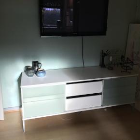 Flot hvid tv bord/skab med to skyde låger af glas og to store skuffer 🌸 - på det sidste billede kan i se, at der er et hul igennem, det er til ledninger og kabler osv.  Står i Randers ved min mor, som kører ofte mod København eller Aalborg 📍  Mål:  Længde: 170,50 cm Højde: 66 cm Dybde: 50 cm  I er meget velkommen til at byde ☺️  I rigtig flot stand 👌🏼
