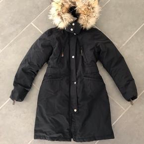 Få en kvalitetsjakke til halv pris!!  Virkelig lækker Eskimo dun jakke i sort til piger med stor lækker fyldig pels hætte jakken kan spændes ind i taljen. og går ned over numsen.  Jakken er både vindtæt, vand afvisende og åndbar og har praktiske ribkanter indvendig ved ærmerne som holder den god tæt  Jakken er med forstærket membran og tapede sømme, der holder vind og vejr ude og børnene dejlig varme og tørre.  Jakken er med aftagelig hætte som sidder på med trykknapper og pelsen kan lynes af og på seperat med lynlås.    *Den ægte pels på hætten er certificeret af Saga Fur   Model: 434 Girls Eskimo down coat w/fur       Pasform: Normal i størrelsen  Materiale: 71% polyamide 29%polyurethane Vaskeanvisning: Kan maskin vaskes ved 30 grader