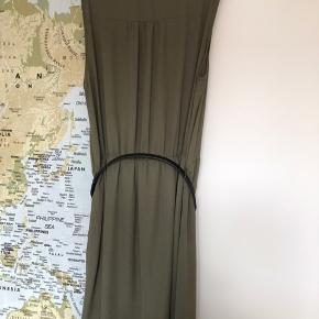 Fin army grøn kjole, med tilhørende bælte og elastik i taljen. Knapper ned til taljen og brystlommer. Går ca. til knæene og med underkjole fra taljen og ned.  Har aldrig været brugt.