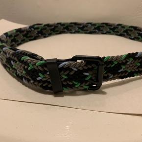 Multifarvet (sort, grå, grøn, blå) unisex elastisk bælte i knyttet materiale. Længde uden spænde ca 130 cm og ca 3 cm bredt Kanter i begge ender samt strap r imiteret skind / PU