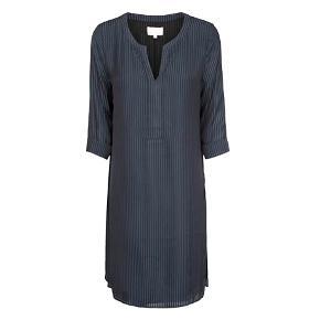 Let og elegant kjole, med striber i blå nuancer. Kjolen har v-udskæring, 3/4 lange ærmer med knappede manchetter, og slids i siderne. Tilføj sneakers for et cool hverdagslook, eller flotte strømper og hæle til festlige begivenheder.