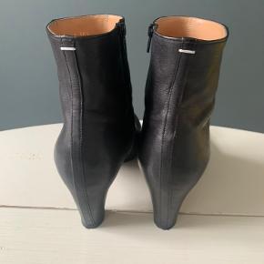 Smukke støvler fra Maison Martin Margiela. Sort, blødt skind, som er trukket ned over hælen, hvilket giver støvlen et mere elegant udtryk. Støvlerne har runde snuder og syv cm hæl. Størrelsen er størrelse 38,5. Sælges for 649 plus porto.